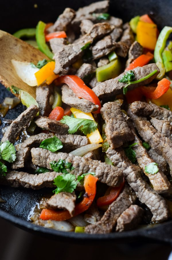 skillet of cooked beef fajita meat with a wooden spoon